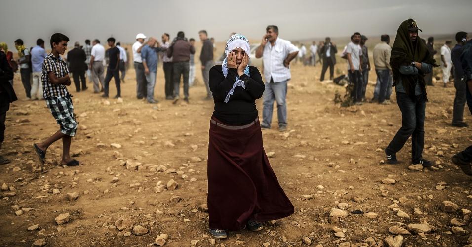 24.set.2014 - Uma mulher síria curda limpa os olhos durante uma tempestade de areia em uma colina onde e ela e outras pessoas observavam confrontos entre jihadistas do Estado Islâmico e combatentes curdos, no vilarejo de Swedi, a 10 km a oeste de Suruc, na província de Sanliurfa, na Síria, nesta quarta-feira (24). Centenas de milhares de curdos sírios entraram na Turquia fugindo da violência