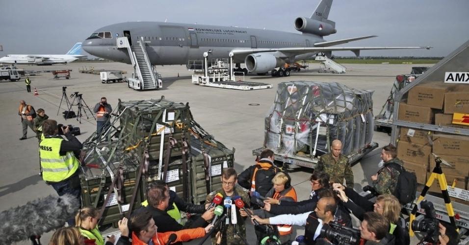 24.set.2104 - Homem dá entrevista para imprensa enquanto militares carregam armas para um avião de transporte da força aérea holandesa no aeroporto de Leipzig, na Alemanha. O carregamento marca o início do fornecimento de armas no valor de 70 milhões de euros para a luta contra o Estado Islâmico (EI)