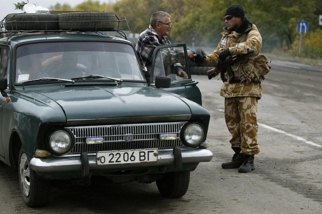 25.set.2014 - Um soldado ucraniano inspeciona um carro no posto de controle perto da cidade de Debaltseve, nesta quinta-feira (25). O presidente ucraniano, Petro Poroshenko, afirmou nesta quinta-feira (25) que o pior da guerra com os insurgentes pró-Rússia no leste do país já passou e anunciou que solicitará a adesão à União Europeia (UE) em 2020