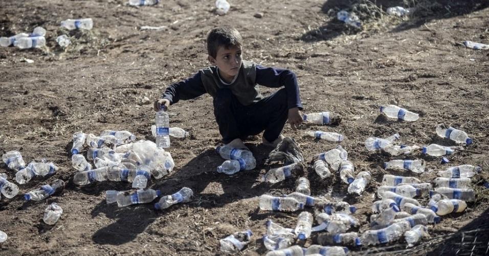 26.set.2014 - Menino curdo recolhe garrafas de água lançadas por curdos turcos em direção à Síria, perto de Sanliurfa. Militantes do grupo que se autodenomina