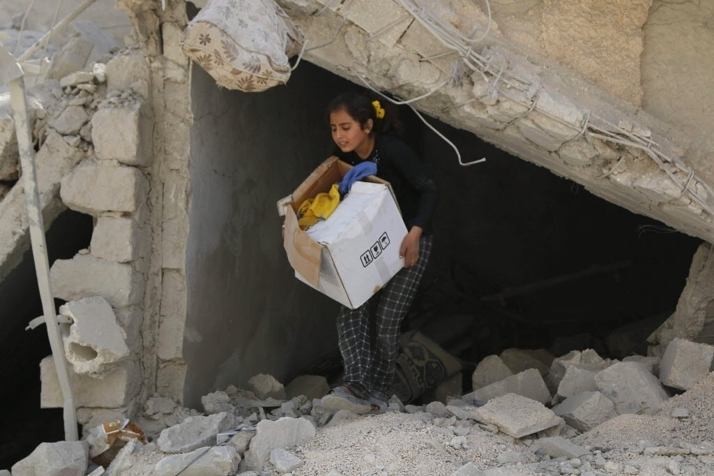 26.set.2014 - Uma menina carrega seus pertences entre os escombros de um prédio destruído em um local que ativistas afirmam ter sido atacado por bombas das forças do presidente da Síria Bashar al-Assad no bairro de al-Sakhour, de Aleppo, na Síria, nesta sexta-feira (26)