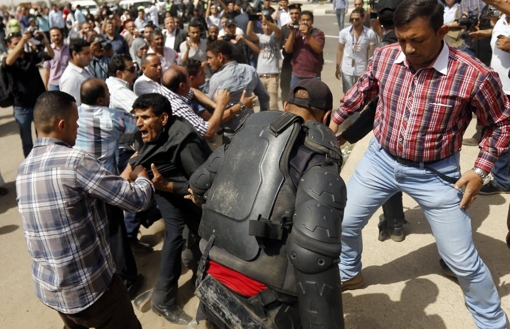 27.set.2014 - Homem que perdeu parentes durante a revolução de 2011 é detido por policiais após confrontos com partidários do ex-presidente egípcio Hosni Mubarak, no Cairo, Egito. O Tribunal Penal do Cairo adiou neste sábado para o próximo dia 29 de novembro a leitura da sentença do julgamento de Mubarak pela morte de manifestantes durante a revolução
