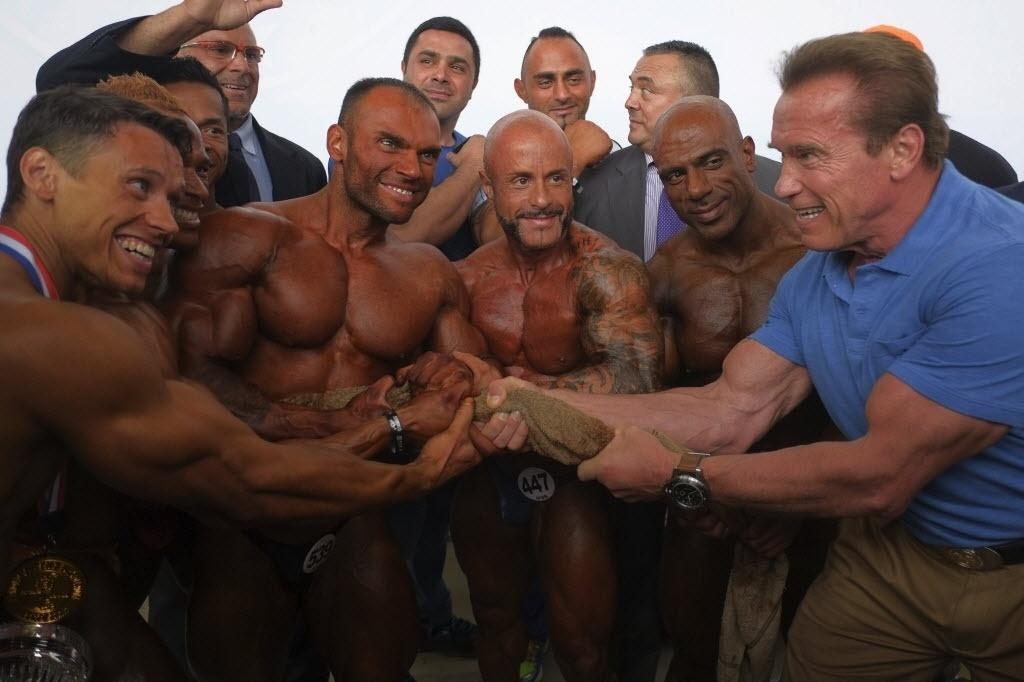 28.set.2014 - O ator e ex-governador da Califórnia (EUA), Arnold Schwarzenegger posa com participantes durante uma competição de fisiculturismo em Madri, Espanha