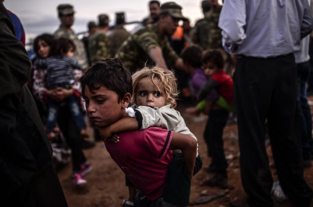 29.set.2014 - Crianças chegam na fronteira entre a Síria e a Turquia depois de vários ataques de morteiros na província de Sanliurfa, nesta segunda-feira (29). Centenas de curdos sírios fogem para Turquia devido aos ataques feitos pelo Estado Islâmico (EI)