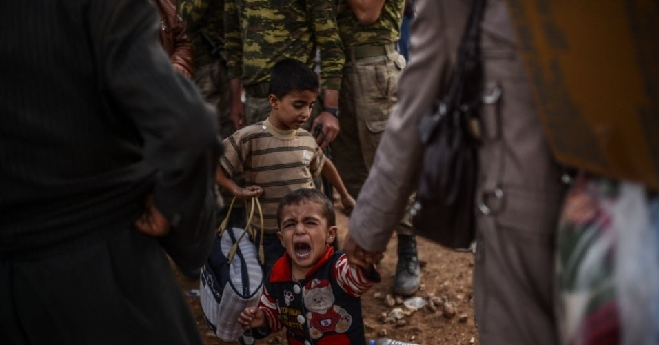 30.set.2014 - Criança chora após atravessar a fronteira entre a Síria e a Turquia depois que vários morteiros atingiram ambos os lados, perto da cidade de Suruc, na província de Sanliurfa, na segunda-feira (29) - a foto só foi divulgada nesta terça-feira (30). Milhares de curdos sírios fugiram para a Turquia por conta dos ataques do Estado Islâmico (EI)