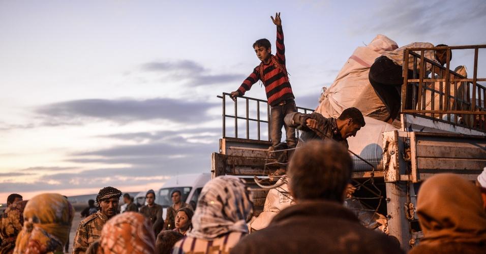 30.set.2014 - Curdos sírios colocam os seus pertences em uma caminhonete na cidade de Sanliurfa, depois de cruzar a fronteira entre a Síria e a Turquia. Milhares de refugiados sírios migraram para a Turquia para fugir dos atentados do Estado Islâmico