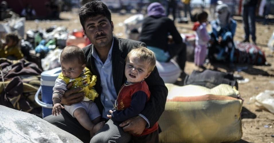 1º.out.2014 - Uma família curda síria aguarda para poder atravessar a fronteira entre a Síria e a Turquia, na cidade de Suruc, na província de Sanliurfa, nesta quarta-feira (1º). Dezenas de milhares de sírios podem ser forçados a fugir de sua terra natal, já devastada por uma guerra civil, se o Estado Islâmico (EI) continuar a ganhar terreno, disse Valerie Amos, chefe da agência humanitária da Organização das Nações Unidas (ONU).