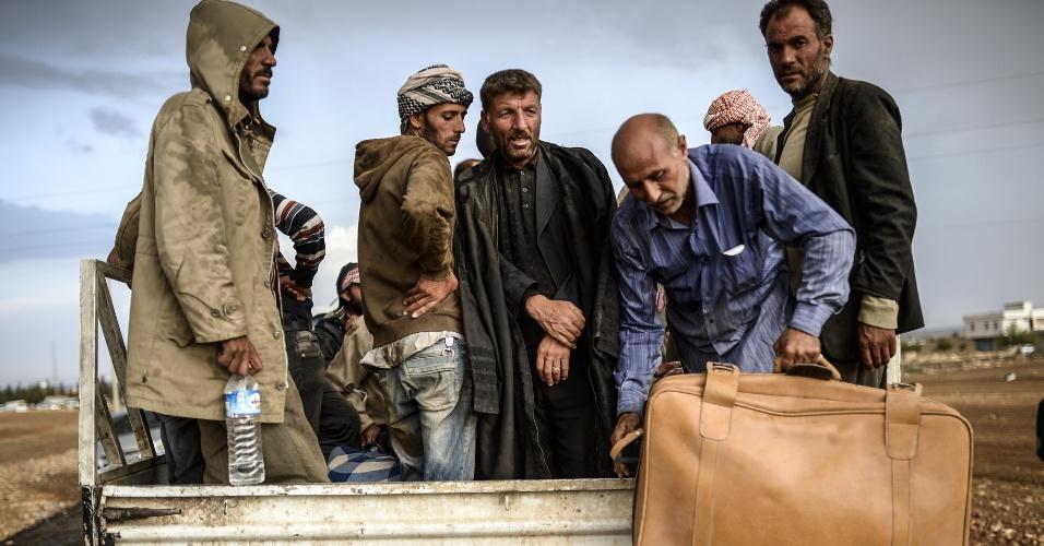 2.out.2014 - Grupo de curdos sírios se acomoda em um veículo na província de Sanliurfa, depois de cruzar a fronteira entre a Síria e a Turquia. Combatentes do Estado Islâmico estão empurrando o conflito em direção a uma cidade curda na fronteira da Síria com Turquia