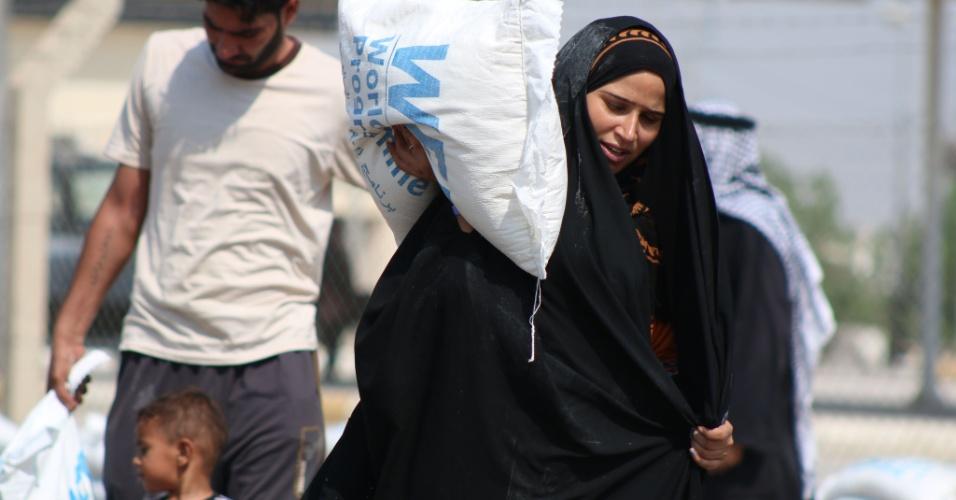 2.out.2014 - Refugiados iraquianos, que deixaram as suas casas após uma ofensiva liderada pelo Estado Islâmico, recebem sacos de comida doados pelo Programa Alimentar Mundial na cidade de Basra, no Iraque. Valerie Amos, chefe humanitário da ONU, disse que as agências das Nações Unidas estão em busca de mais financiamento para ajudar quase duas milhões de pessoas deslocadas por causa da violência no Iraque
