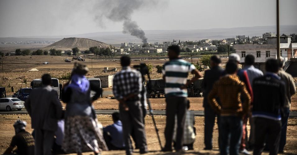 3.out.2014 - Pessoas observam fumaça após ataque à cidade síria de Kobani, perto da fronteira entra a Síria e a Turquia. O governo da Turquia informou que vai fazer o que puder para evitar que a cidade de Kobani, predominantemente curda, seja dominada pelos insurgentes do Estado islâmico