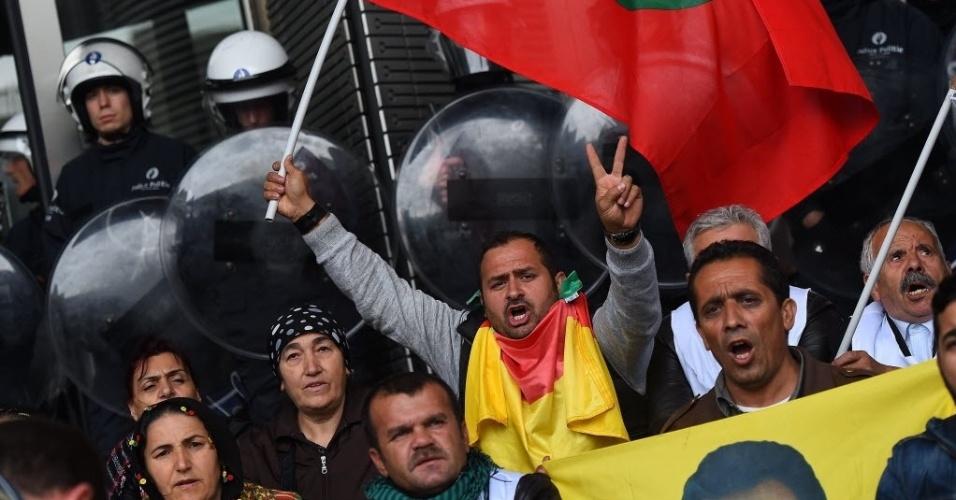 7.out.2014 - Manifestantes entoam palavras de ordem enquanto seguram bandeira do Partido dos Trabalhadores do Curdistão, enquanto a polícia faz guarda em frente à entrada do Parlamento Europeu durante manifestação pedindo apoio para a cidade curda síria de Kobani, que está sendo atacada pelo grupo Estado Islâmico (EI), nesta terça-feira (7), em Bruxelas, na Bélgica. Mais de 100 manifestantes curdos invadiram a sede do Parlamento para protestar pela passividade da União Europeia (UE) diante dos ataques terroristas do EI