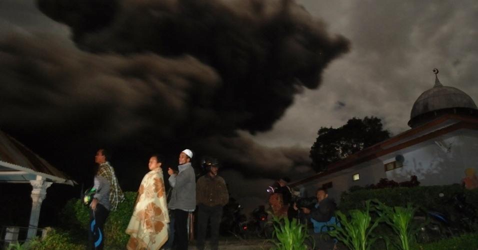 7.out.2014 - Moradores se reúnem fora de suas casas no distrito de Karo e observam uma nuvem de cinzas, resultante da erupção do vulcão Sinabung, que encobre parte da ilha indonésia de Sumatra, nesta terça-feira (7). Centenas de moradores ainda estão alojados em centros de evacuação depois da erupção do vulcão no dia 5 de outubro que matou cerca de 17 pessoas