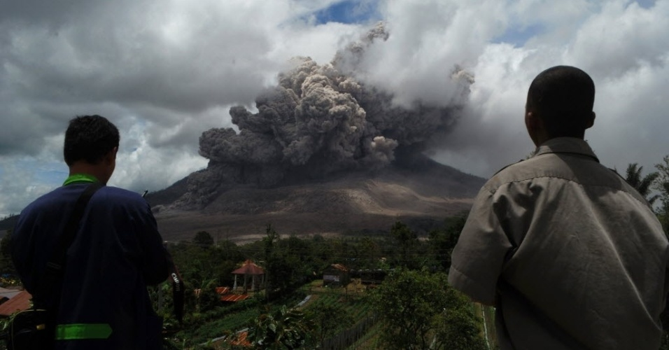 8.out.2014 - Moradores observam do distrito de Karo nuvens de cinzas que são expelidas do Monte Sinabung, localizado na ilha indonésia de Sumatra, nesta quarta-feira (8). De acordo com as autoridades, centenas de moradores ainda estão alojados em centros de evacuação após a erupção do início de fevereiro, que matou cerca de 15 pessoas