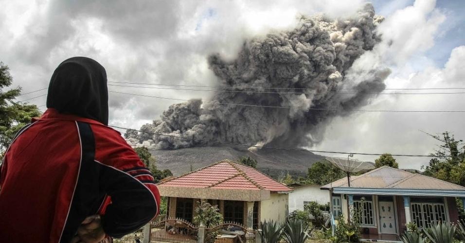 8.out.2014 - Uma mulher observa a erupção do vulcão Sinabung, na província de Sumatra, na Indonésia. O vulcão entrou em erupção em fevereiro deixando 15 mortos e forçando milhares de pessoas a deixarem suas casas