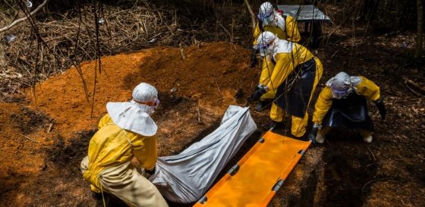 Equipe funerária enterra o corpo de um homem que morreu após contrair ebola na Libéria