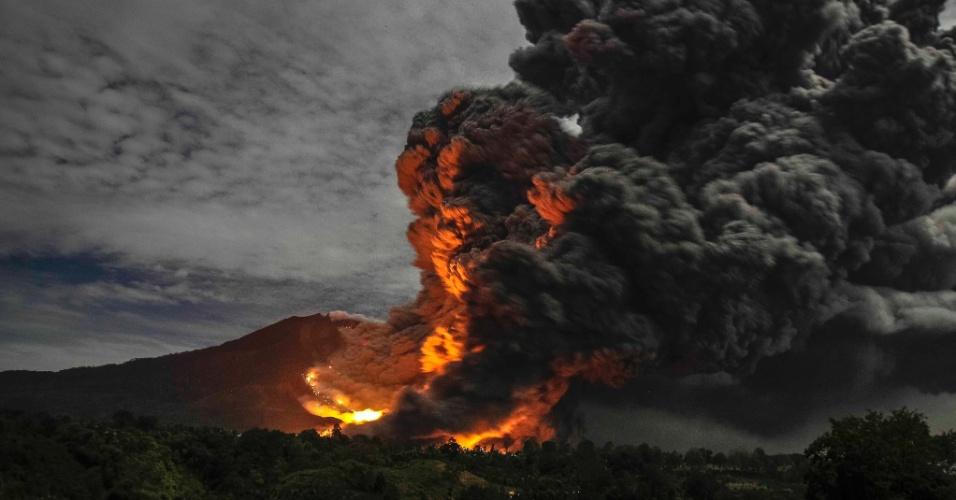 8.out.2014 - O Monte Sinabung entra em erupção, visto da aldeia Tiga Pancur, na Província de Sumatra do Norte, na Indonésia; O vulcão entrou em erupção em agosto de 2010 pela primeira vez em 400 anos, e está ativo desde setembro. Ao menos 16 pessoas morreram em decorrência das erupções neste ano e mais de 25 mil tiveram que ser evacuadas