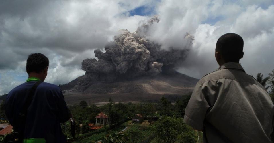 9.out.2014 - Moradores observam as nuvens cinzas que sobem da cratera do vulcão no Monte Sinabung, na quarta-feira (8), na ilha de Sumatra, na Indonésia. O vulcão entrou em erupção em agosto de 2010 pela primeira vez em 400 anos, e está ativo desde setembro. Ao menos 16 pessoas morreram em decorrência das erupções neste ano e mais de 25 mil tiveram que ser evacuadas