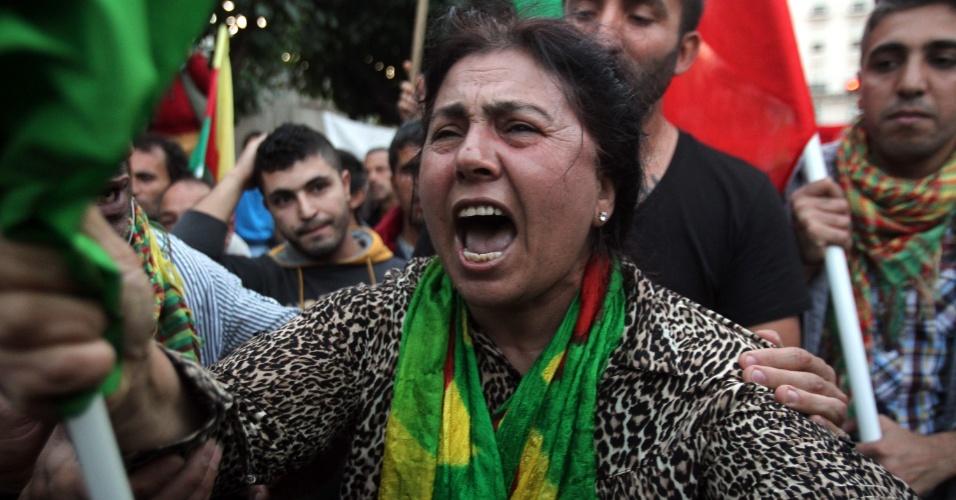 13.out.2014 - Uma mulher curda que vive na Grécia participa de protesto contra os ataques lançados por militantes do Estado Islâmico que têm como alvo a cidade síria de Kobane e a falta de ação por parte do governo turco, no centro de Atenas, na Grécia, nesta segunda-feira (13)