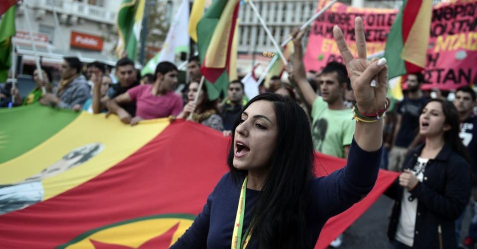 13.out.2014 - Uma mulher participa de protesto contra os ataques lançados por militantes do Estado Islâmico que têm como alvo a cidade síria de Kobane e a falta de ação por parte do governo turco, no centro de Atenas, na Grécia, nesta segunda-feira (13)