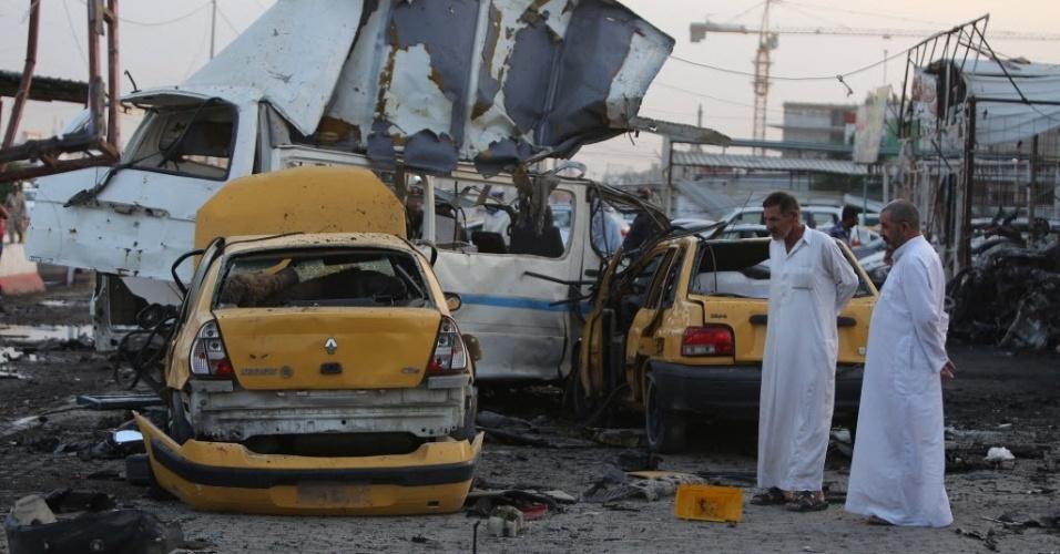 14.out.2014 - Homens inspecionam local da explosão de um carro-bomba em Bagdá, no Iraque, nesta terça-feira (14). De acordo com a polícia local, ao menos 22 pessoas morreram no atentado