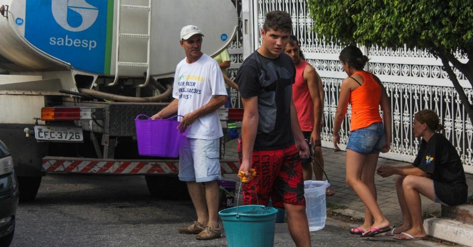 14.out.2014 - Moradores da Vila São Pedro, na zona sul de São Paulo, enchem baldes de água em caminhão-pipa, no sexto dia de falta de água na região. As torneiras das casas localizadas nas ruas Niderau Felix Machado e Domingos Luiz Bueno estão secas desde o dia 8 de outubro