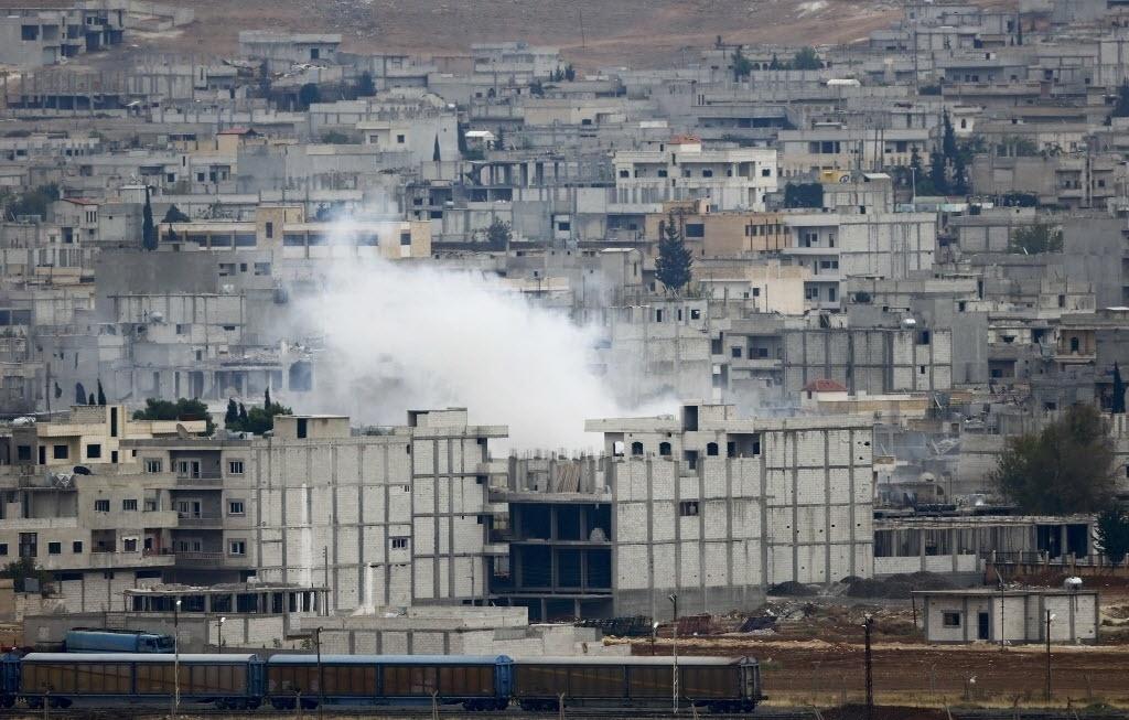 17.out.2014 - Fumaça sobe entre prédios na cidade síria de Kobani, em fotografia feita da fronteira entre Síria e Turquia, na cidade turca de Suruc. Curdos de nacionalidade síria têm protestado contra o governo turco devido à ausência de ações da Turquia contra os radicais sunitas do Estado Islâmico, que cercaram a cidade curda de Kobane, na Síria