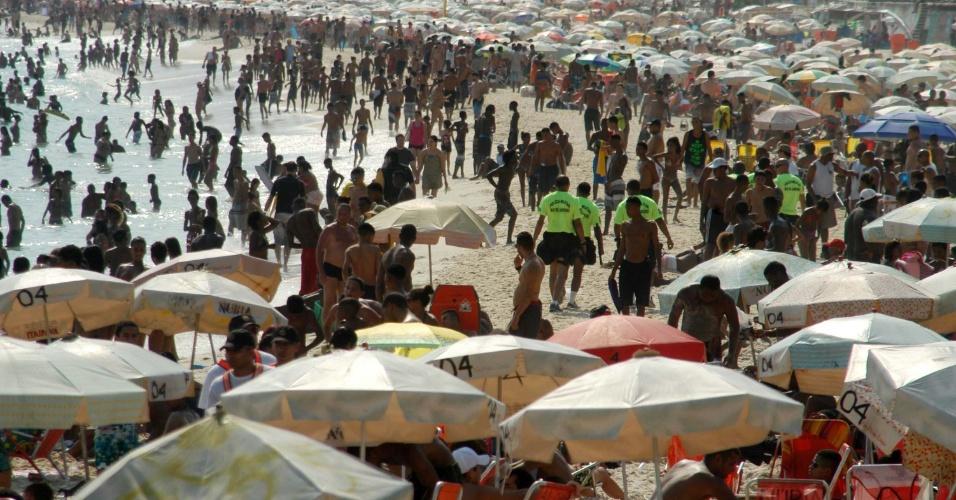 19.out.2014 - Banhistas lotam a praia do Arpoador, no Rio de Janeiro, que teve a segurança na orla reforçada. Agentes com camisetas verdes circulam para tentar coibir crimes. A previsão de temperatura máxima para este domingo (19) é de 40ºC na cidade