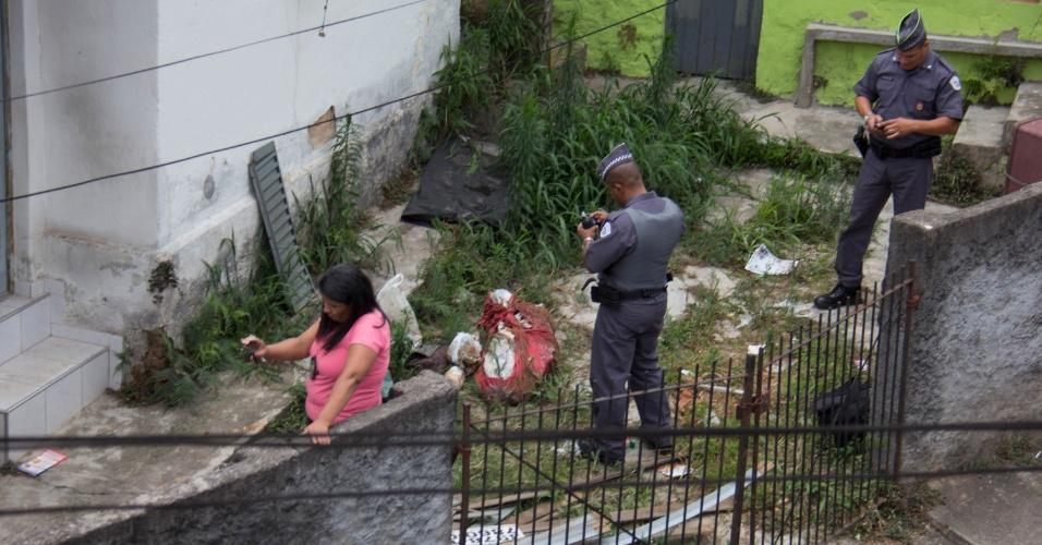 20.out.2014 - Bombeiros e policiais trabalham na remoção de restos mortais de um corpo encontrado enterrado no quintal de uma casa na rua Pedro de Oliveira Simões, no bairro da Freguesia do Ó, em São Paulo, nesta segunda-feira (20). O corpo é possivelmente da garota Jaqueline, que estava desaparecida, mas ainda passará por perícia. O principal suspeito é o namorado dela