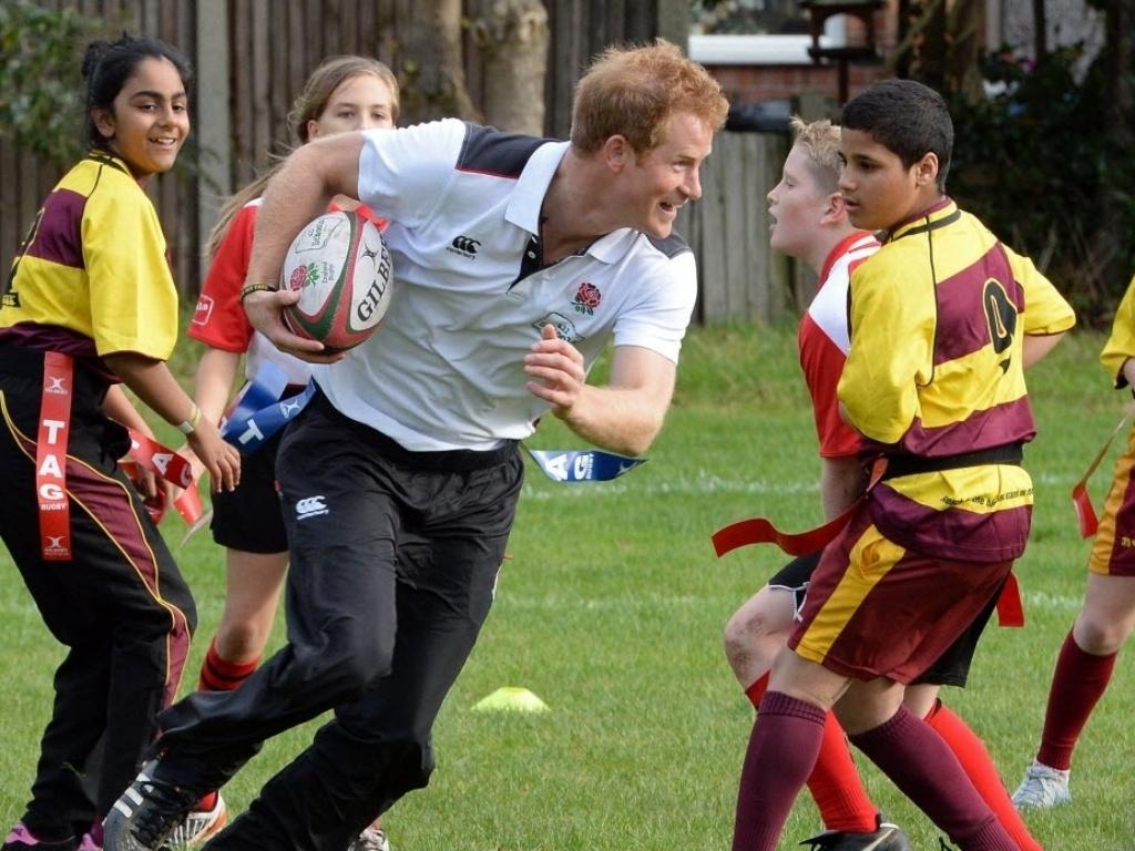 20.out.2014 - O príncipe britânico Harry brinca com crianças durante um festival de rúgbi, em Eccles, noroeste de Inglaterra
