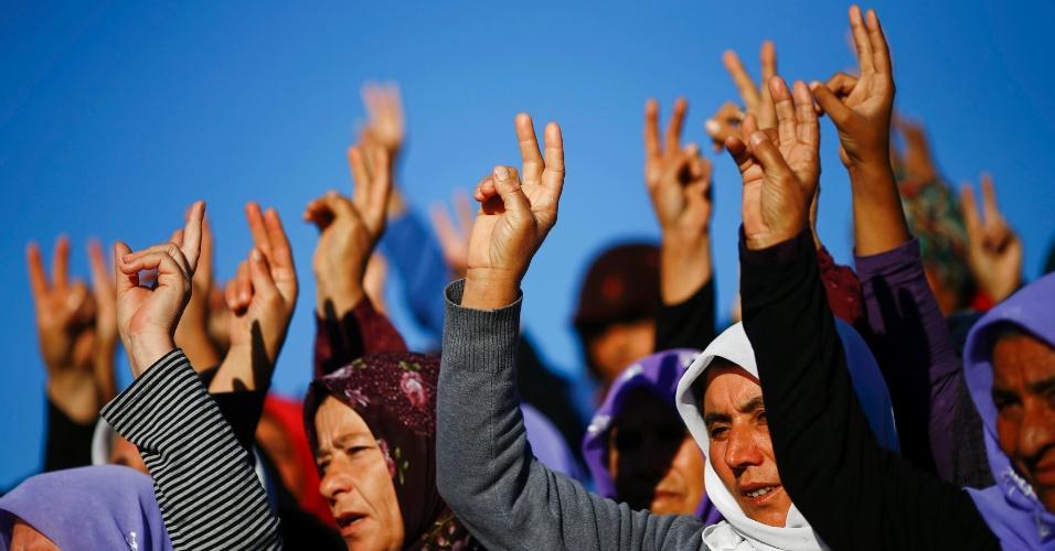21.out.2014 - Mulheres turcas fazem o sinal da vitória durante funeral de combatentes curdos mortos em conflito contra o Estado Islâmico na cidade síria de Kobani, fronteira com a Turquia