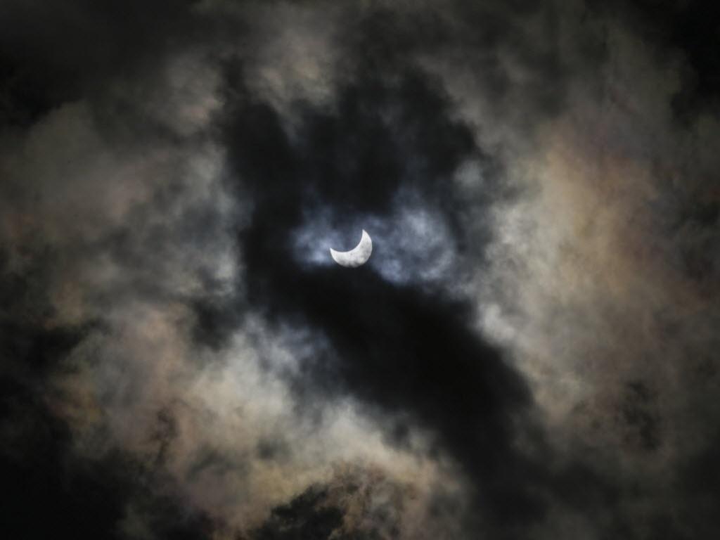 24.out.2014 - ECLIPSE PARCIAL DO SOL - Um eclipse parcial do Sol é retratado entre nuvens em Bellingham (Washington), nos Estados Unidos. Segundo a Nasa (agência espacial americana), o eclipse pode ser visto em grande parte da América do Norte