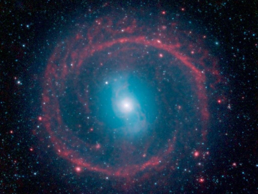 24.out.2014 - ESTRELAS JOVENS E VELHAS NA GALÁXIA ? Imagem obtida pelo telescópio infravermelho Spitzer, da Nasa (agência espacial americana), mostra estrelas jovens e antigas em ação na galáxia NGC 1291, localizada na constelação de Erídano. O anel externo, de cor vermelha, aparece repleto de novas estrelas que estão acendendo e aquecendo o pó. As estrelas na área central são mais velhas e tem cor azul, elas ficam localizadas nessa área, pois já utilizaram todo o gás disponível para criar novas estrelas. A galáxia é considerada ?barrada?, pois uma barreira de estrelas (que parece um S, na parte azul da imagem) domina seu centro