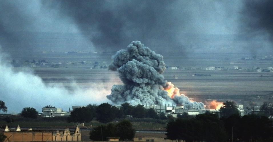 25.out.2014 - Nuvem de fumaça e poeira é vista após ataque aéreo na cidade síria de Kobani, na fronteira com a Turquia nesta sexta-feira (24). Os jihadistas do grupo Estado Islâmico (EI) realizaram neste sábado (25) um novo ataque em direção à fronteira com a Turquia, ao norte de Kobani