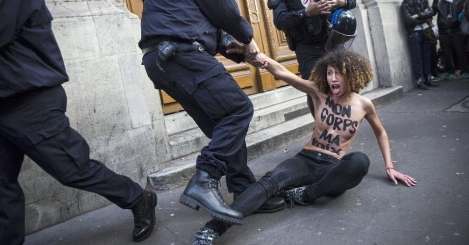 26.out.2014 - Militante do grupo Femen é retirada da frente do Palácio de Justiça por um policial, em Paris, França. O grupo protesta contra acusações de
