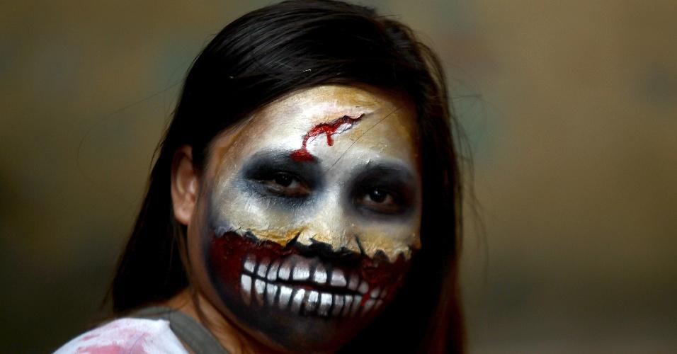 """26.out.2014 - Menina fantasiada de zumbi posa para foto durante a festa """"Zombie Zumba"""", na cidade de  Mandaluyong, nas Filipinas, em comemoração ao Halloween. Mais de 500 pessoas participaram do evento"""