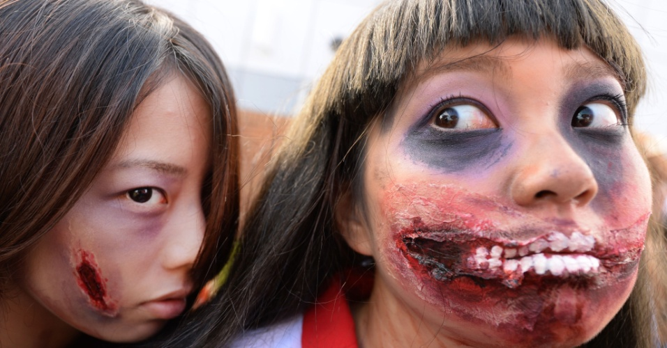 26.out.2014 - Meninas maquiadas como zumbis posam para foto antes de desfile de Halloween em Kawasaki, um subúrbio de Tóquio, no Japão. Mais de 100 mil pessoas assistiram ao desfile de pessoas fantasiadas e mais de 2.500 participaram dele