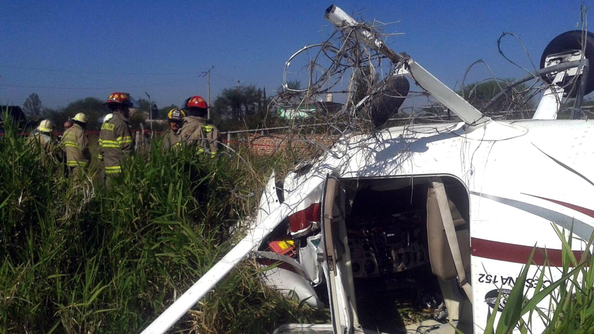 27.out.2014 - Bombeiros vasculham os destroços de um pequeno avião que caiu num terreno baldio no município de Tlajomulco de Zuñiga, no México, nesta segunda-feira (27). De acordo com informações das autoridades locais, não houve mortes