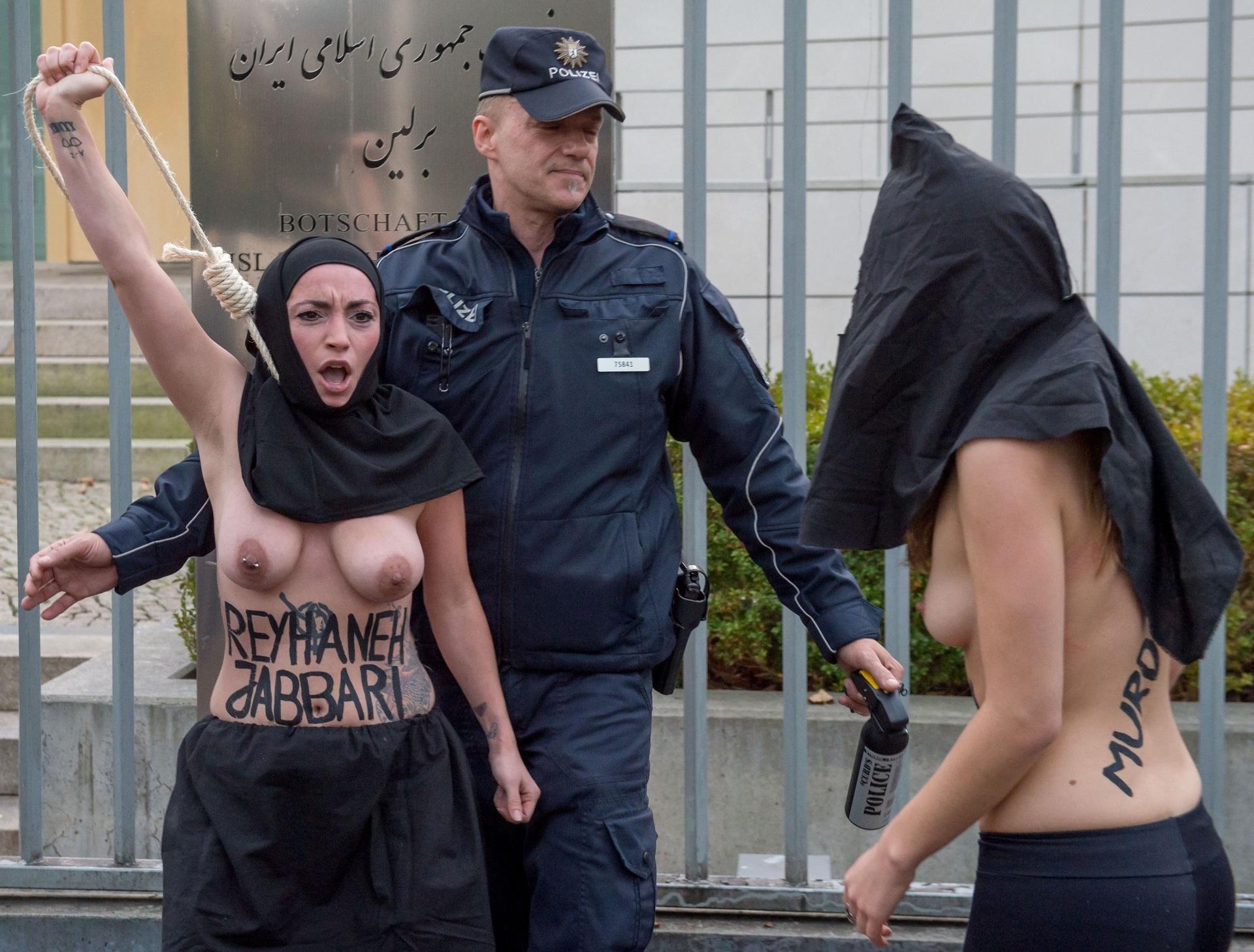 27.out.2014 - Policial reprime manifestantes do grupo feminista Femen que protestam em frente à embaixada iraniana em Berlim (Alemanha), nesta segunda-feira (27). O grupo protesta contra a execução no Irã de uma mulher condenada por ter matado um homem que ela acusava de ter tentado estuprá-la