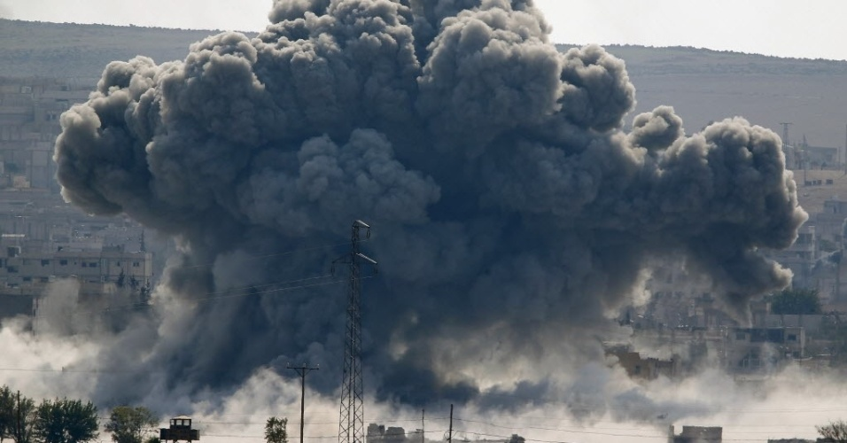 28.out.2014 - Uma explosão na sequência de um ataque aéreo cobre de fumaça a cidade síria de Kobani na fronteira com a Turquia. Ao todo, 815 pessoas morreram em 40 dias de ofensiva do grupo jihadista Estado Islâmico (EI) contra o enclave, segundo o Observatório Sírio de Direitos Humanos