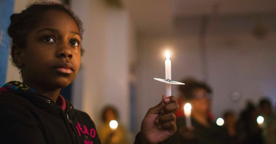 29.out.2014 - Garota segura vela durante vigília em memória aos dois anos da chegada do furacão Sandy, na Igreja do Nazareno na comunidade Rockaway, em Nova York, nesta quarta-feira (29)