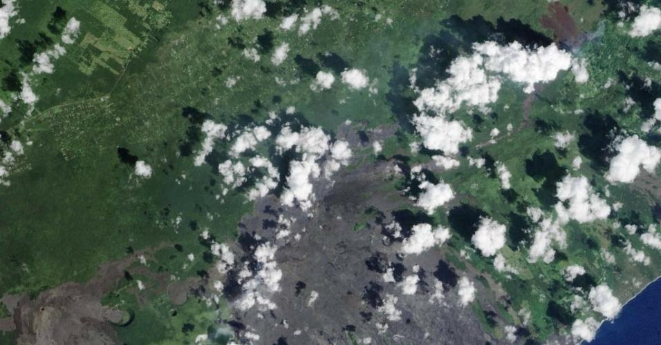 29.out.2014 - RIO DE LAVA - Imagem feita no dia 24 de outubro pelo satélite da Nasa mostra o fluxo de lava do vulcão Kilauea, perto da aldeia de Pahoa, no Hawaii. Um rio lento de lava derretida do vulcão em erupção flui através de um imóvel residencial na Ilha Grande, ameaçando dezenas de casas e empresas, segundo as autoridades. A lava foi em direção a cidade de Pahoa por semanas, com velocidade média de 13,7 metros por hora