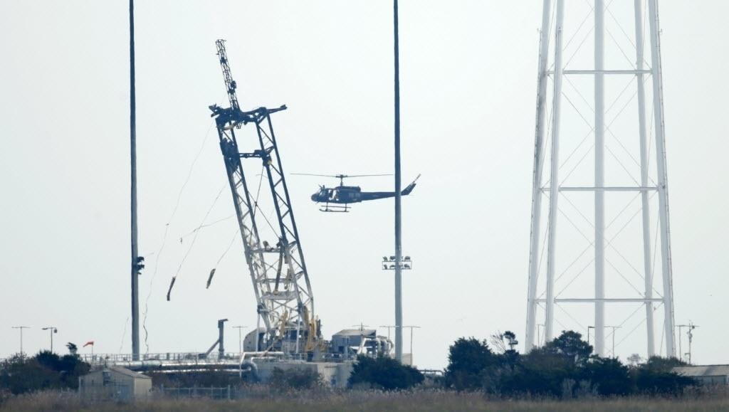 29.out.2014 - Um helicóptero faz o reconhecimento da área da plataforma de lançamento da Nasa na Ilha Wallops, na Virgínia (EUA). As autoridades começaram a investigar a causa da explosão do foguete Antares, da empresa privada americana Orbital Sciences Corporation