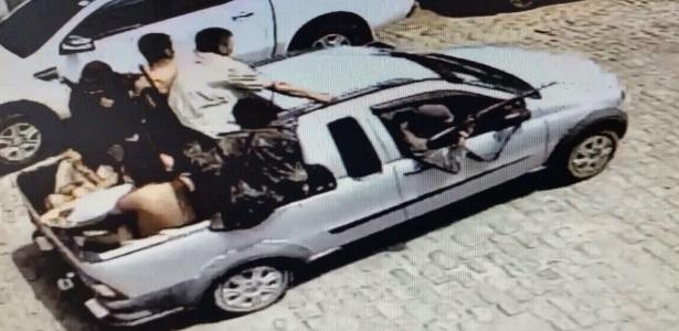 Câmera de segurança mostra pelos menos oito homens fugindo com os dois reféns