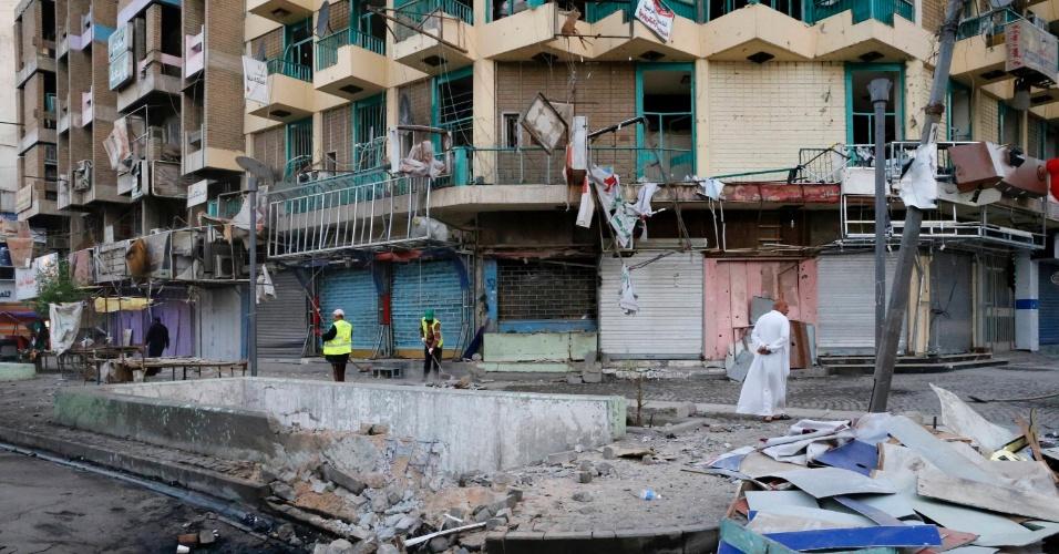 3.nov.2014 - Funcionários limpam o local de um ataque com carro-bomba em Bagdá, nesta segunda-feira (3). A explosão matou ao menos oito peregrinos xiitas segundo autoridades. Os muçulmanos xiitas, maioria no Iraque, se preparam para o festival religioso de Ashura, evento que no passado já foi marcado por violentos atentados suicidas