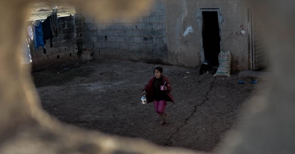 4.nov.2014 - Garota anda pelo quintal de sua casa na aldeia a sudeste de Mursitpinar, na província de Sanliurfa, local em que os jihadistas do EI (Estado Islâmico) vem cometendo uma série de abusos contra adolescentes, incluindo tortura