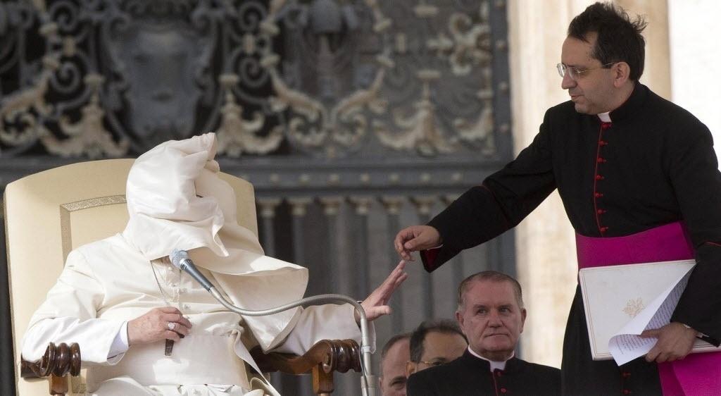 5.nov.2014 - Rosto do papa Francisco é coberto pelo amito de sua roupa após rajada de vento durante audiência na Praça de São Pedro, no Vaticano