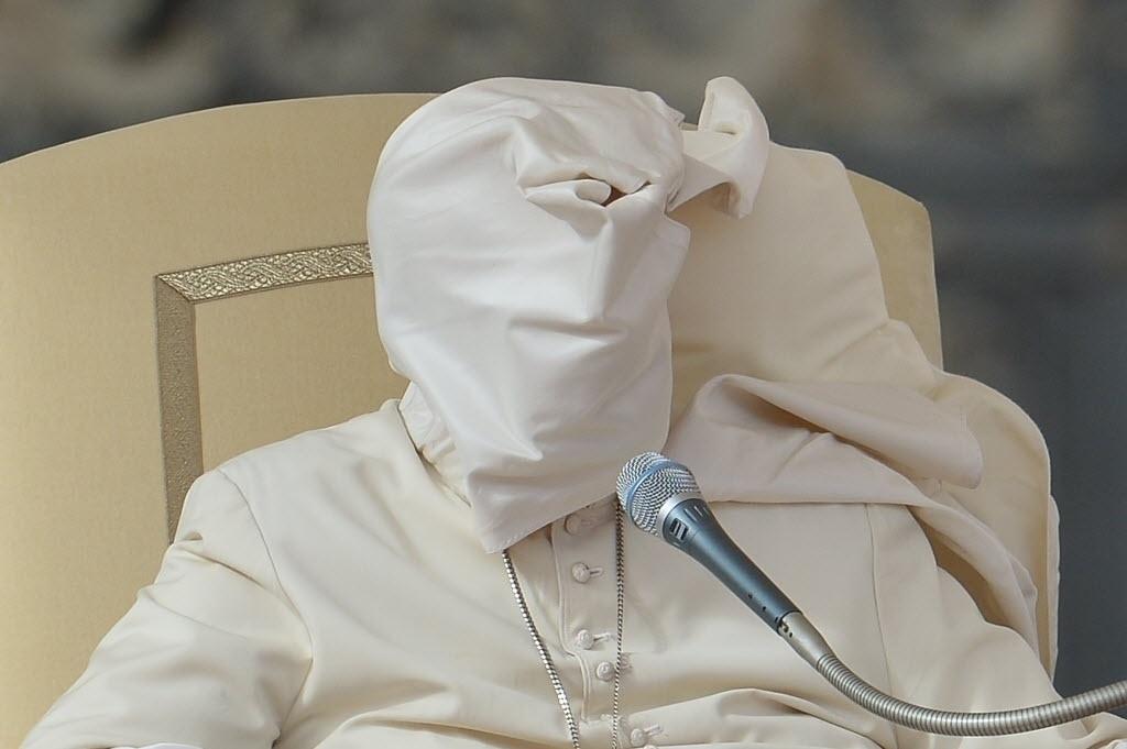 5.nov.2014 - Uma rajada de vento levantou o amito da roupa do papa Francisco e cobriu o rosto dele durante missa semanal na praça de São Pedro, no Vaticano, nesta quarta-feira (5)