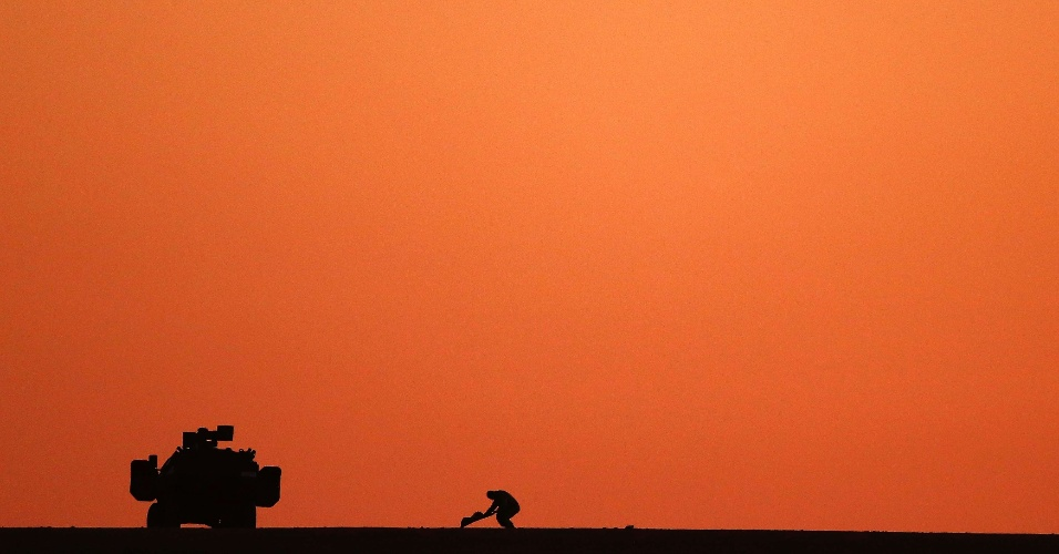 5.nov.2014 - Soldado turco estende tapete ao lado de veículo militar para realizar suas orações. Da colina pode-se observar o conflito entre tropas curdas e do Estado Islâmico na cidade síria de Kobani. Um jornalista curdo, um dos poucos a cobrir o cerco à cidade, que já dura quase dois meses, explica que um dos fatores que mantém a resistência da cidade aos jihadistas é a solidariedade entre os moradores - cerca de 1% da população original - que se manteve em Kobani