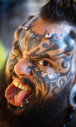 11.out.2014 - O venezuelano Emilio Gonzalez posa para fotos durante a Convenção Internacional de Tatuagem em Bucareste, na România. Ele tem o rosto inteiramente tatuado, além de piercings e modificações na pele