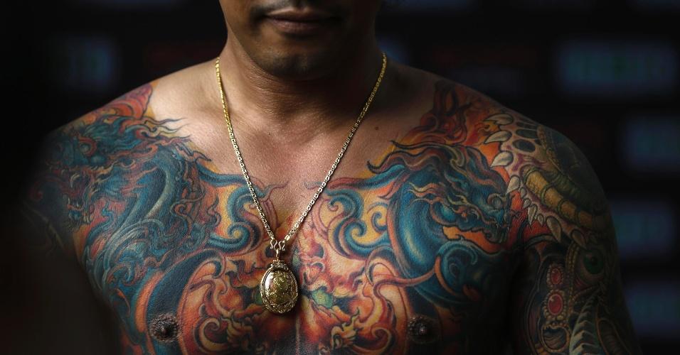 23.out.2014 - Um competidor do Concurso MBK de Tatuagem, realizado em um shopping center de Bancoc, mostra suas tatuagens na Tailândia